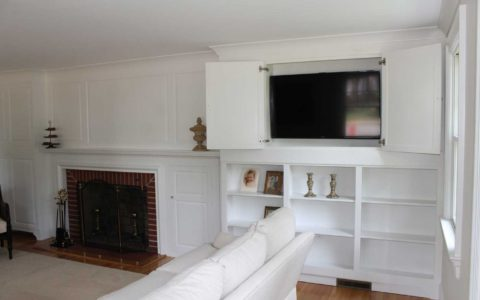 White full-wall design with fireplace, shelving, and hidden TV by MLG Woodworking