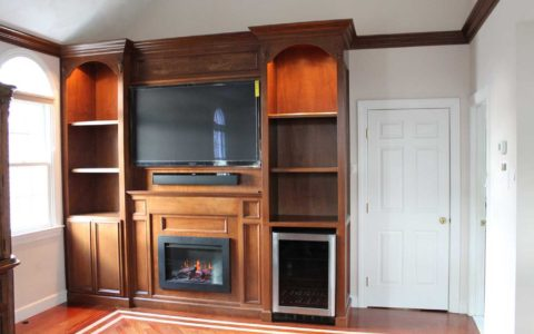 Professionally finished wall unit with TV, fireplace, and wine fridge by MLG Woodworking